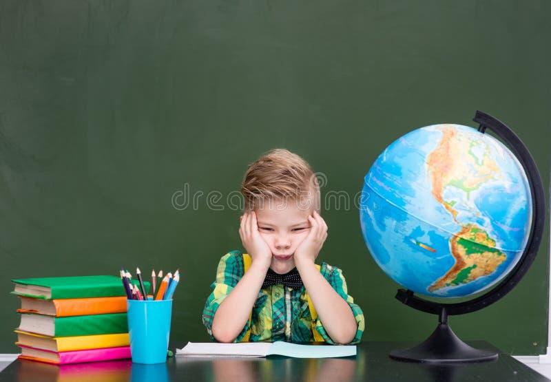 Trött skolpojke i klassrum arkivfoto