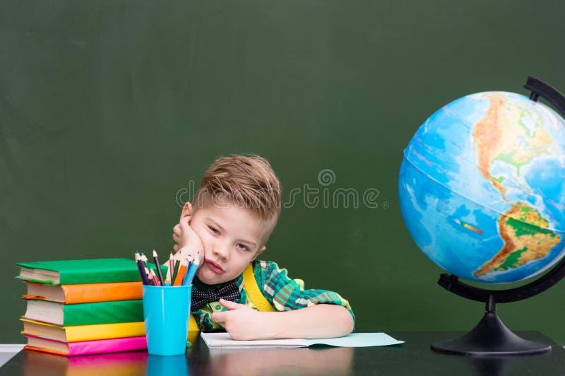 Trött skolpojke i klassrum royaltyfri foto