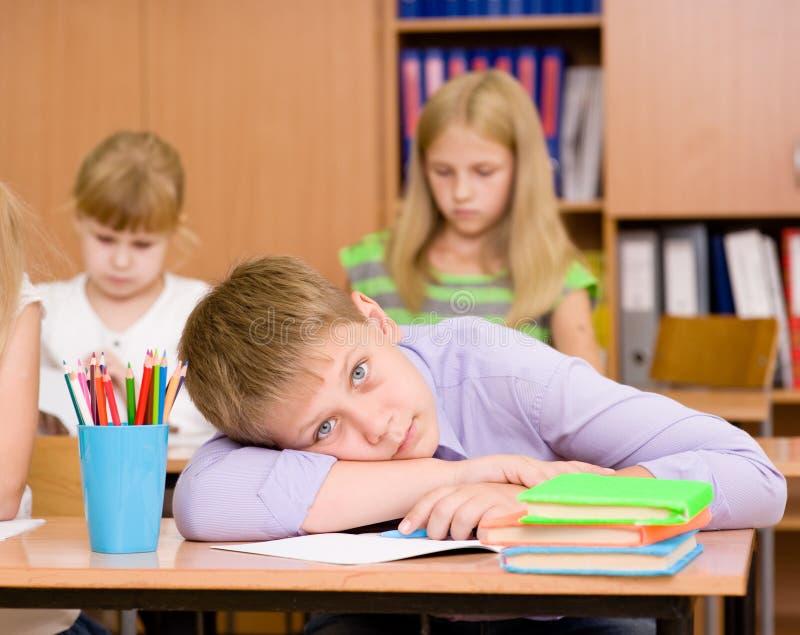 Trött skolpojke på en kurs på skolan arkivbild
