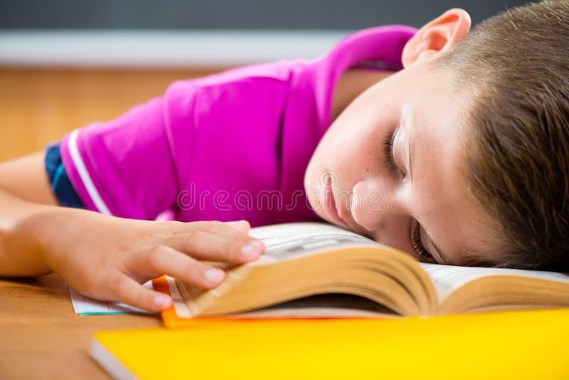 Trött skolpojke som sover på boken arkivbild