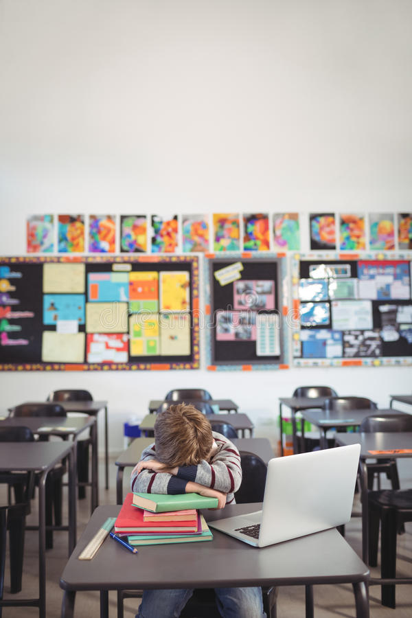 Trött skolpojke som sover på bunt av boksammanträde i klassrum royaltyfri bild
