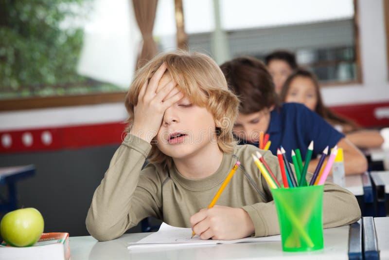 Trött skolpojkesammanträde på skrivbordet i klassrum royaltyfri foto