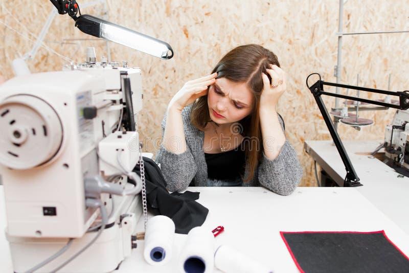 Trött skräddare på hennes arbetsplats med huvudvärk royaltyfri foto