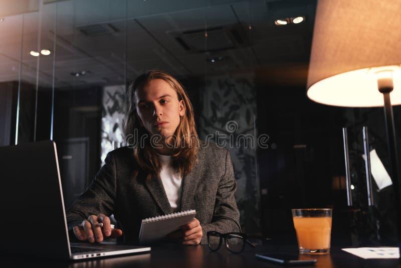 Trött stilfull projektchef som arbetar vid den moderna bärbara datorn på nattkontoret Hipsteren med långt hår sitter vid trätabel royaltyfria foton