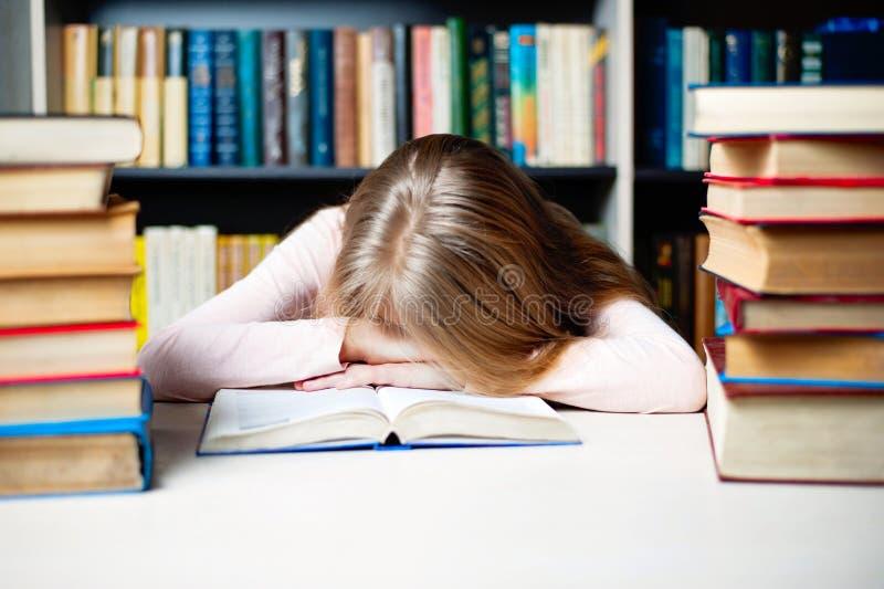 Trött studentflicka med böcker som sover på tabellen utbildning, period, examina och skolabegrepp royaltyfria bilder