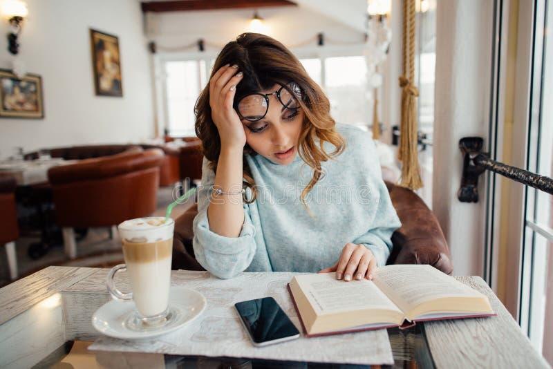 Trött studentflicka som läser vetenskaplig litteratur royaltyfri foto