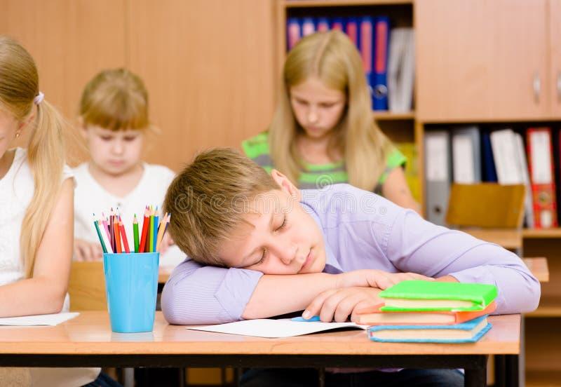 Trött studentpojke som sover i klassrum arkivbilder
