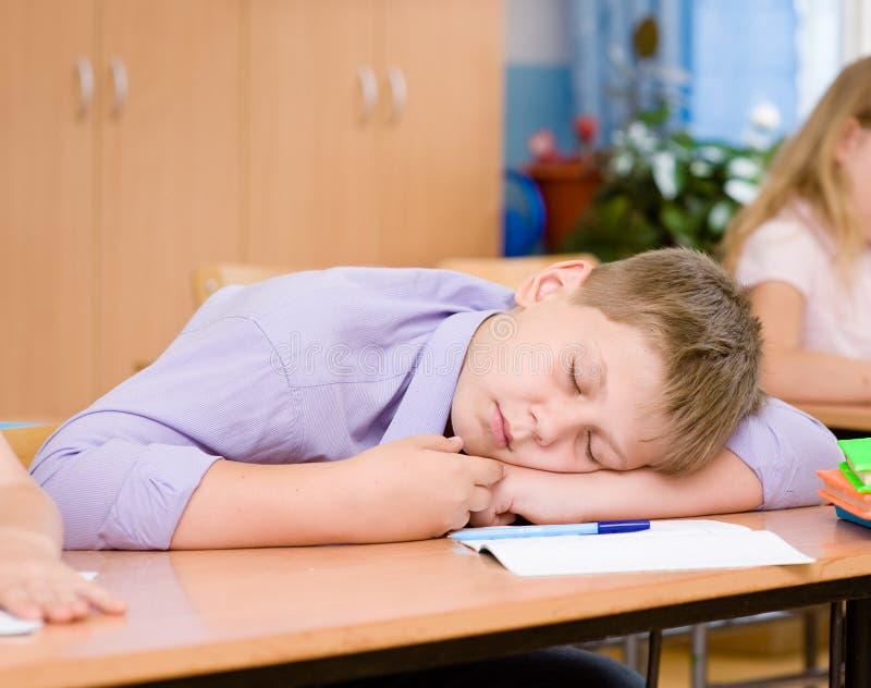 Trött studentpojke som sover i klassrum royaltyfria foton