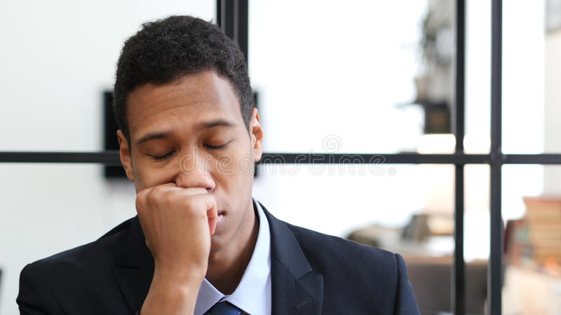 Trött svart affärsman Sleeping på arbete arkivfoton