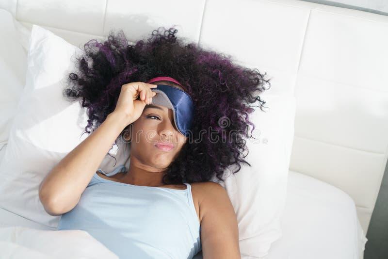 Trött svart flicka som vaknar upp i säng med sömnmaskeringen arkivfoto