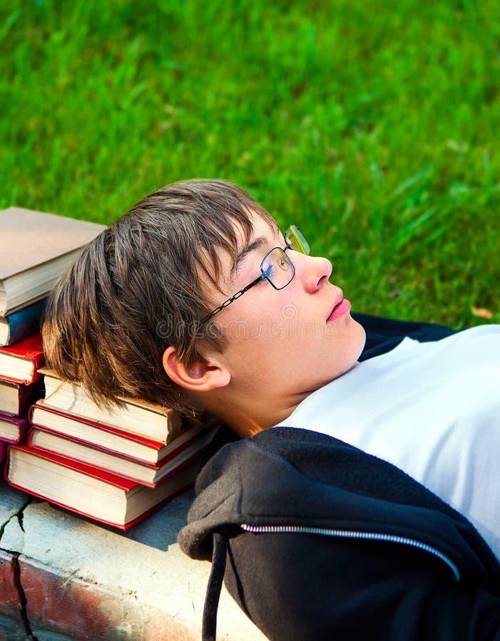 Trött tonåring med böcker royaltyfri bild