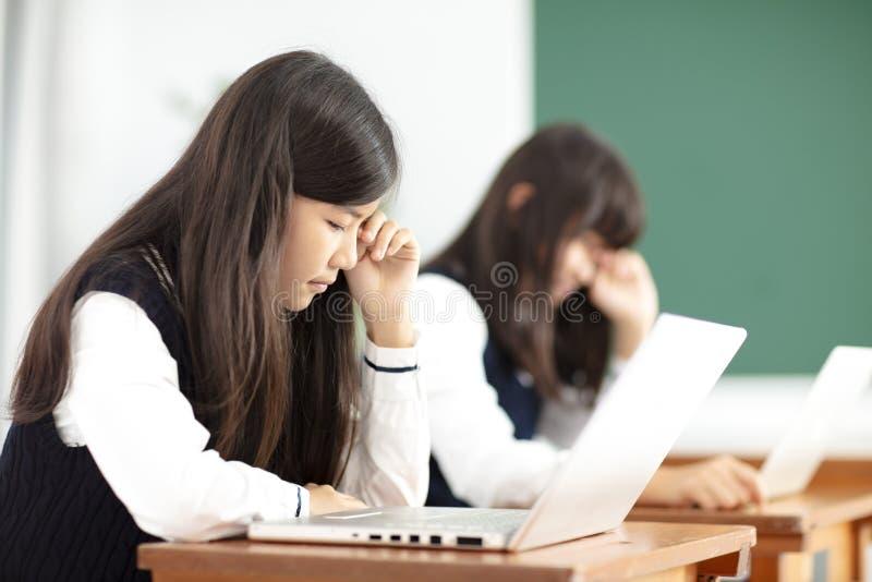 Trött tonåringstudent som studerar med bärbara datorn i klassrum fotografering för bildbyråer