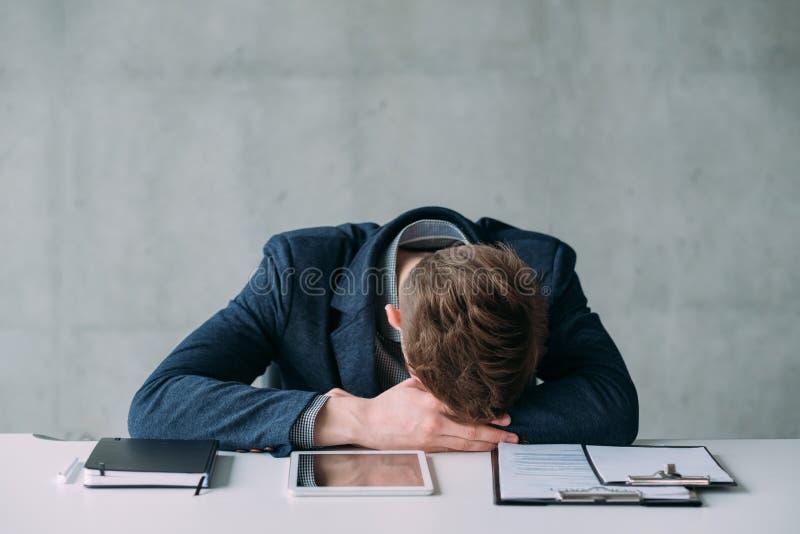 Tr?tt ung chef f?r kontorsrutin som sover arbete royaltyfri bild