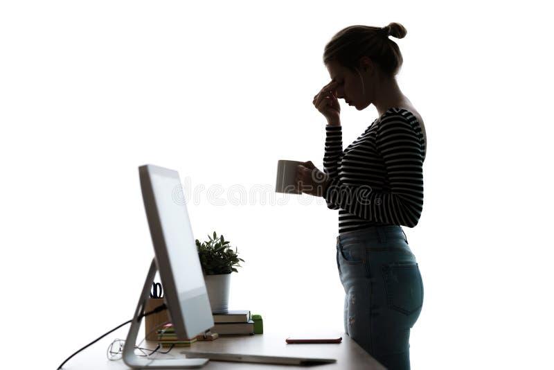 Trött ung kvinna med huvudvärken som framme står av datoren över vit bakgrund royaltyfri foto