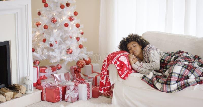Trött ung kvinna som framme ta sig en tupplur av ett Xmas-träd royaltyfria bilder