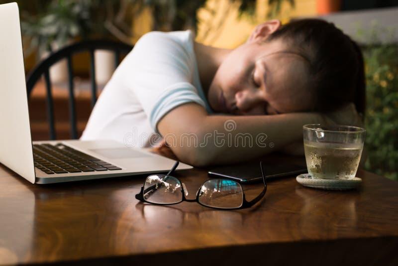 Trött ung kvinna som sover på hennes datorskrivbord royaltyfria bilder