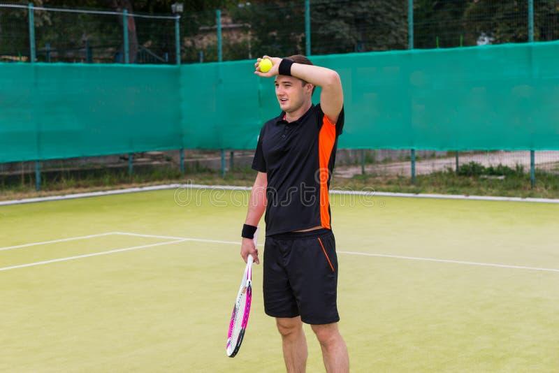 Trött ung manlig tennisspelare efter match royaltyfri bild
