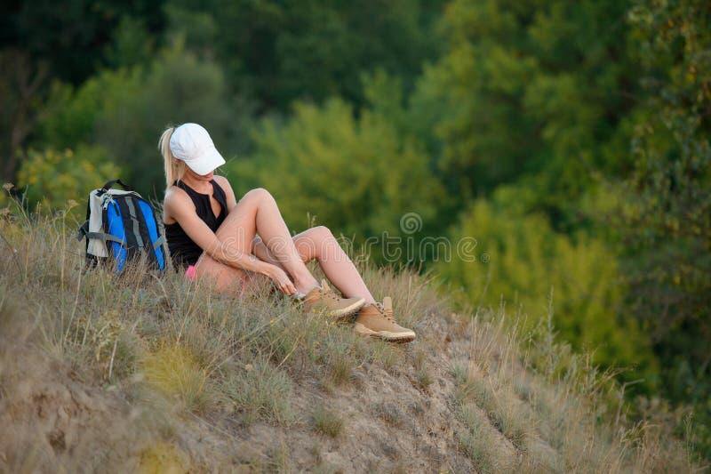 Trött ungt fotvandrarekvinnasammanträde på gräs och tar av dina skor arkivfoton