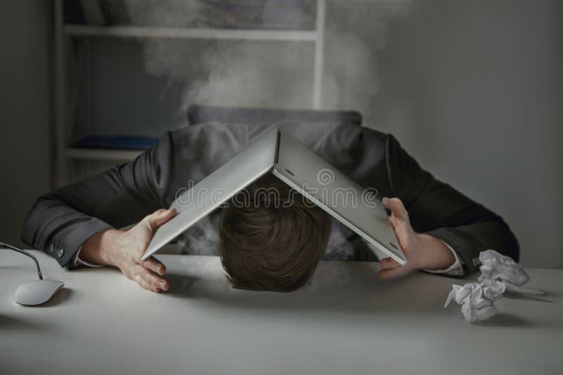 Trött utmattad affärsman med hans huvud som ligger på skrivbordet arkivbilder