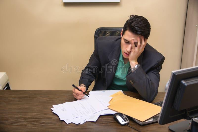 Trött uttråkad ung affärsman som i regeringsställning sitter royaltyfria foton