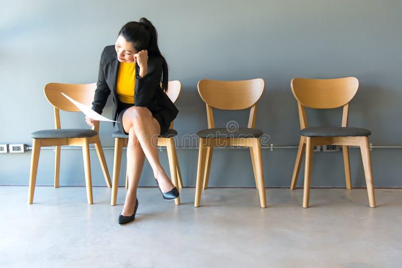 trött vänta Affärskvinnainnehavpapper och se bort, medan sitta royaltyfri bild
