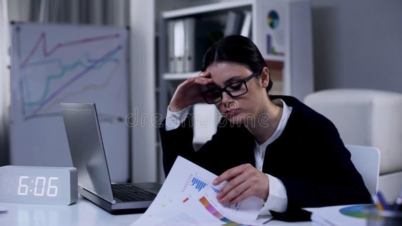 Trötta affärskvinna som läser ekonomisk rapport med diagram, frustrerad av underskott royaltyfri fotografi