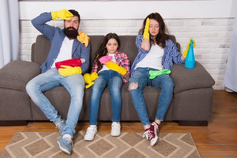 Trötta föräldrar och unge Göra ren hela dagen att evakuera ockupation Evakuera rengörande dag Familjmammafarsa och dotter med royaltyfri bild