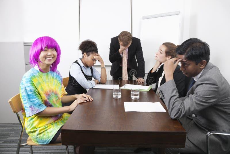 Trötta multietniska businesspeople med kollegan i rosa peruk på mötet arkivfoto
