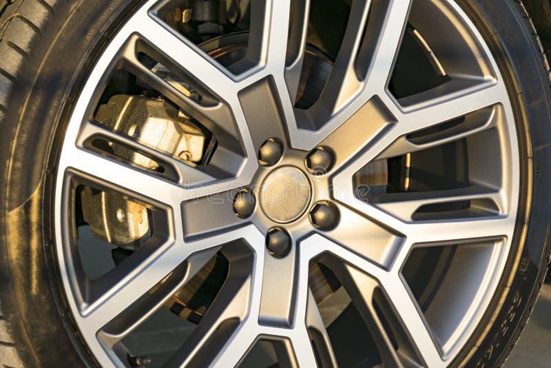 Trötta och legera hjulet av en modern bil på jordningen, bilyttersidadetaljer arkivfoton