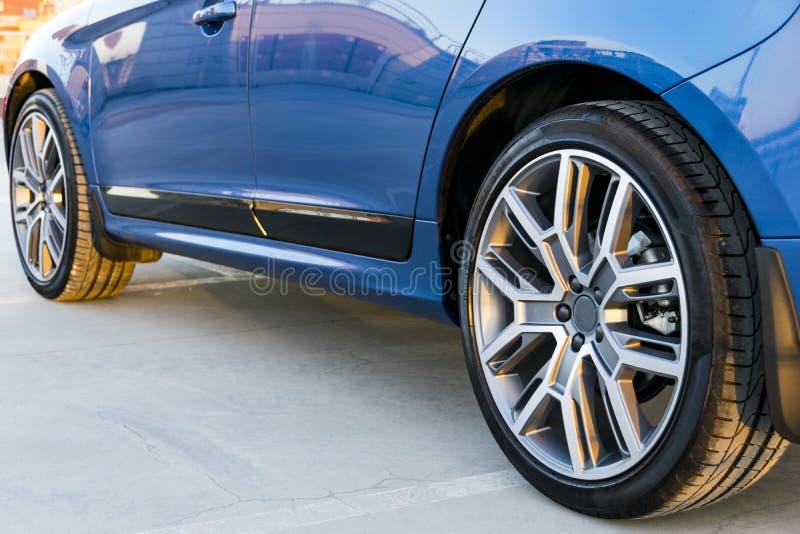 Trötta och legera hjulet av en modern blå bil på jordningen, bilyttersidadetaljer royaltyfri bild