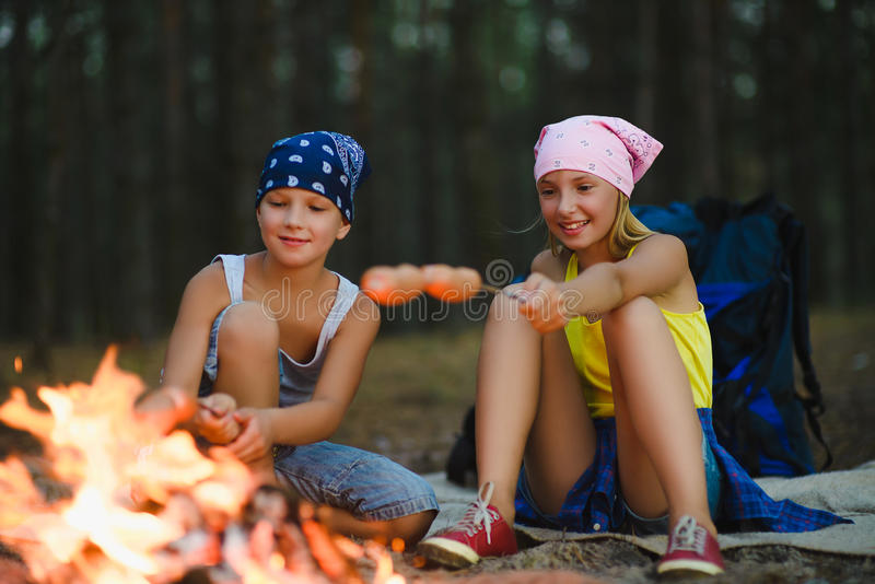 Trötta och lyckliga ungar som sitter på lägereld och stekte korvar royaltyfria foton