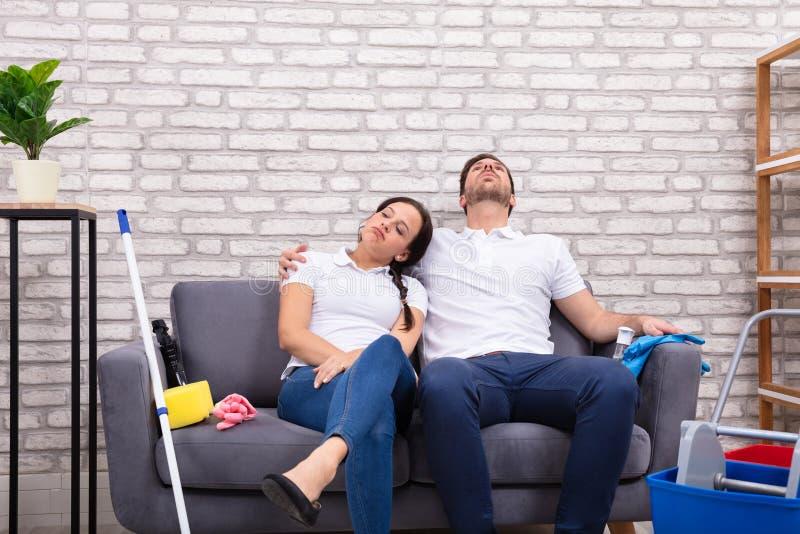 Tr?tta par som sitter p? soffan royaltyfri bild