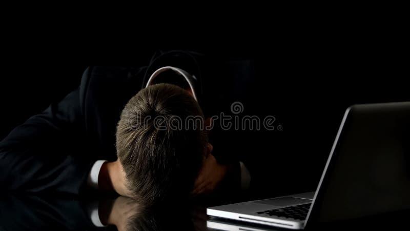 Tröttad affärsman som ligger på den främsta bärbara datorn för tabell, förfallen stopptid, överansträngning fotografering för bildbyråer