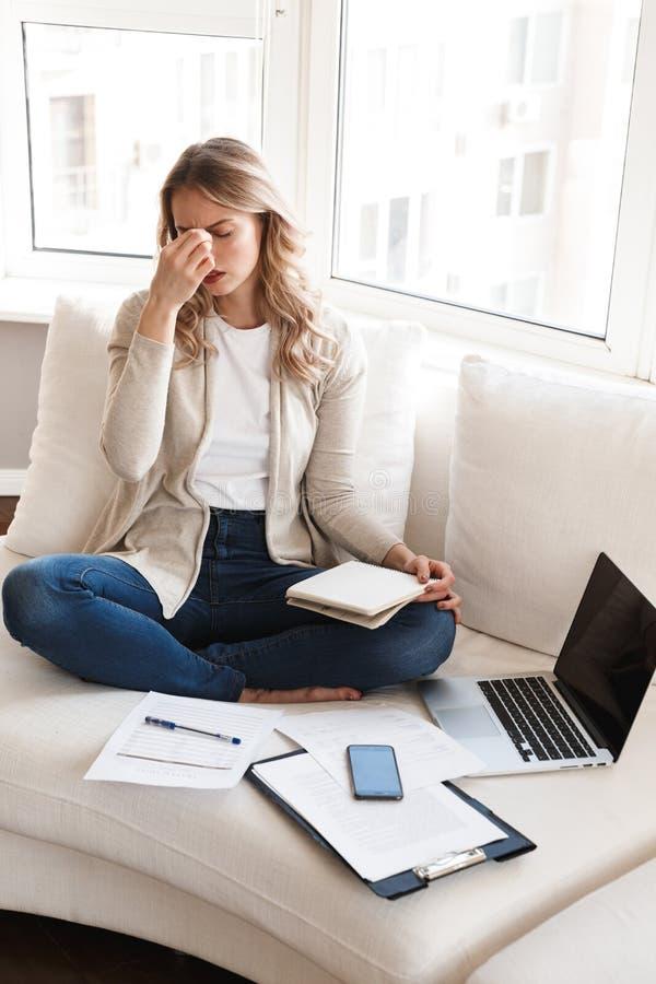 Tröttad blond kvinna med huvudvärken som poserar att sitta inomhus hemma genom att använda bärbar datordatoren royaltyfri bild