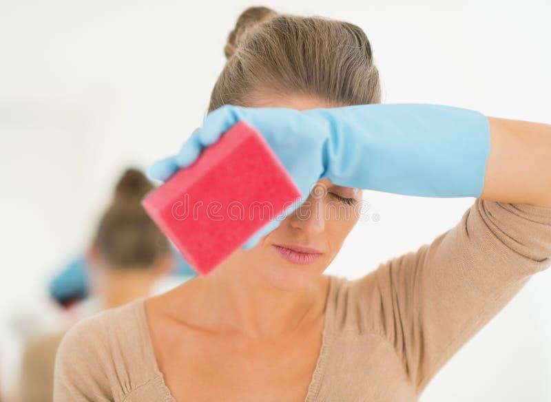 Tröttad hemmafru, medan göra ren arkivfoton