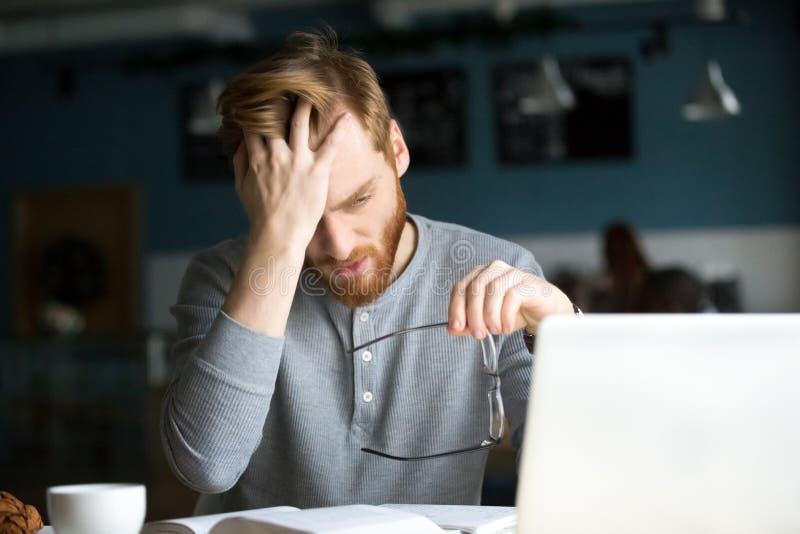 Tröttad man som förargas med svårt studerande sitta i kafé royaltyfri bild