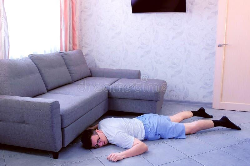 Tröttad rolig nerdman i exponeringsglas och kortslutningar falled till golvet från utmattning hemma royaltyfri bild