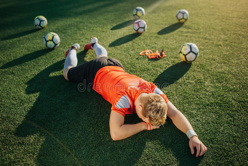 Tröttad ung spelare som ligger på gräsmatta med framsidan som vänds till jordningen Bollar som ligger bak honom Solen skiner utan royaltyfri foto