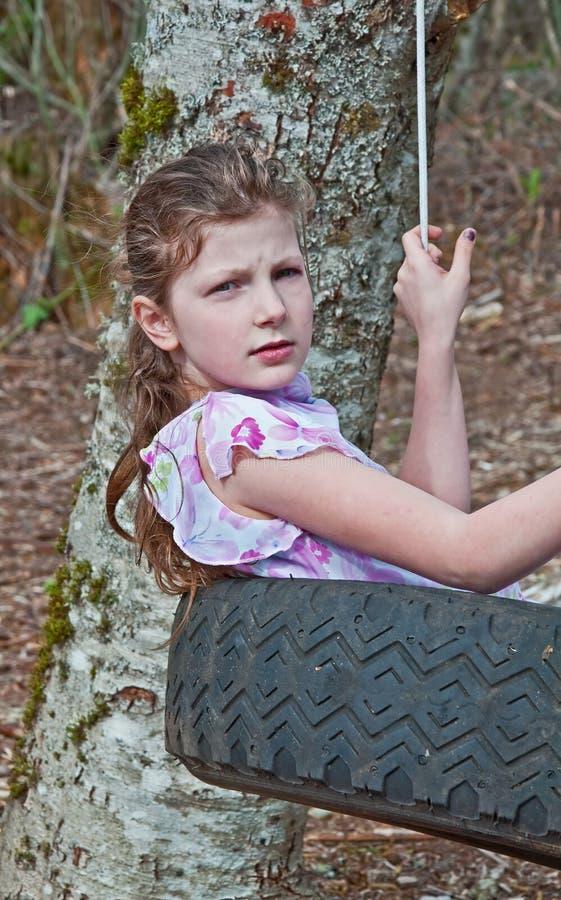 Tröttar årig Caucasian flicka 9 in gunga royaltyfri foto