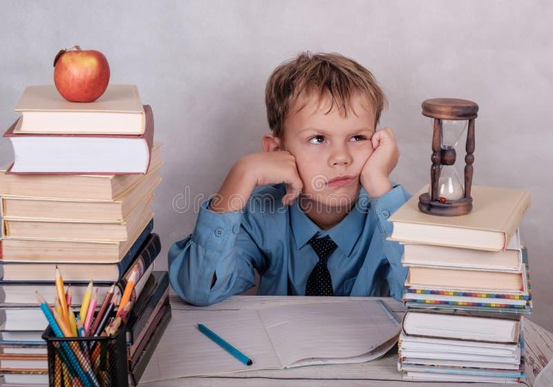 Tröttat av kurserna av den europeiska pojken på tabellen med böcker arkivfoton