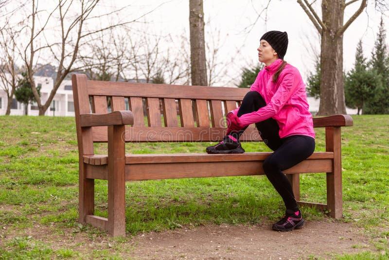 Tröttat eller deprimerat parkerar vila för kvinnlig idrottsman nen på en bänk på en kall vinterdag på utbildningsspåret av ett st royaltyfria foton