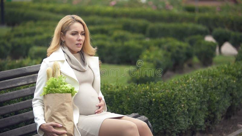 Tröttat gravid kvinnligt sammanträde parkerar påsen för bänkinnehavlivsmedelsbutiken som förväntar trötthet royaltyfri foto