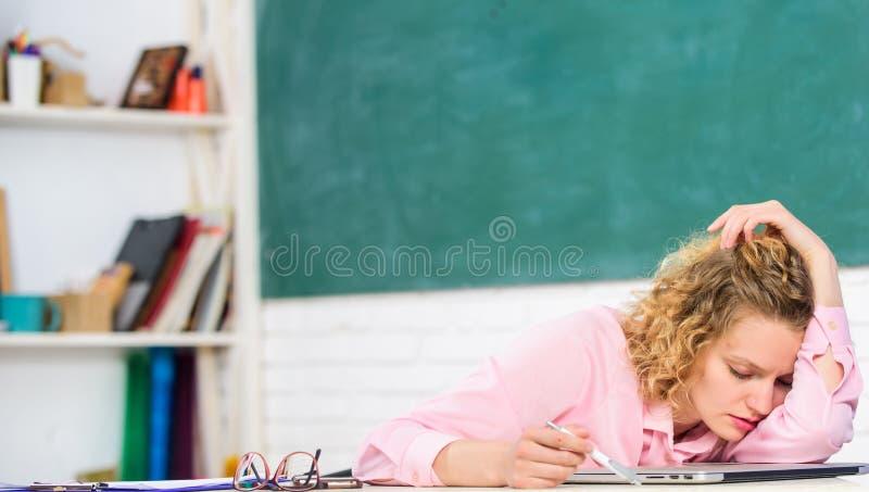 Tröttat handleda nedgången sovande på arbetsplatsen Den tröttade studenten lutar på skrivbordet Evakuera kurs Lärare som evakuera royaltyfri foto