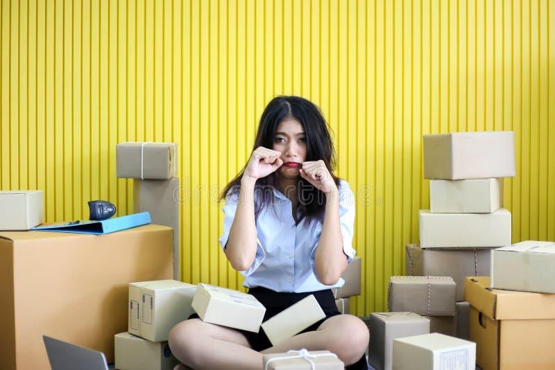 Tröttat olyckligt av den unga asiatiska flickan är freelancerstarten upp adress för handstil för små och medelstora företagägare  arkivbild