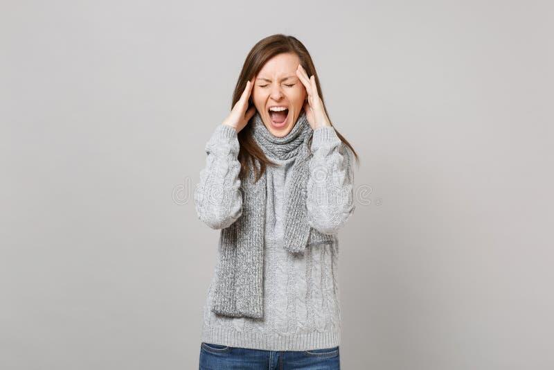 Tröttkörd ung kvinna i den gråa tröjan, halsduk med stängda ögon som skriker sätta på händer på huvudet som har huvudvärk royaltyfria foton