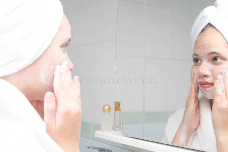Trądzik opieki nastolatek w bathrobe pozycji w łazience przed lustrem zdjęcia royalty free