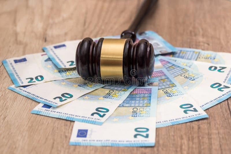 Tr?auktionsklubba med 20 eurosedlar p? skrivbordet arkivbild