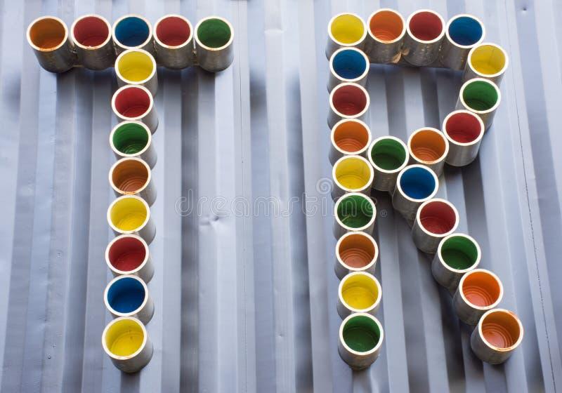 Tr-Buchstaben wie die Abkürzung, die durch bunte Blechdosen gemacht wird, sind auf dunkler Wand als Hintergrund Unter Verwendung  stockfoto