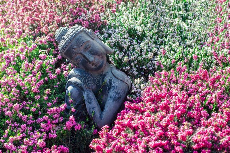 tr?dg?rds- fridsamt Traditionell fridfull buddha statyprydnad med härliga blommor royaltyfri fotografi