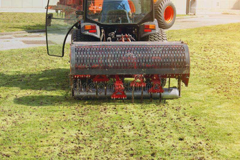 Tr?dg?rdsm?stareOperating Soil Aeration maskin p? gr?sgr?smatta arkivfoto